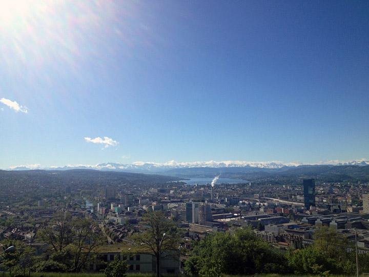 Blick auf Zürich samt Zürisee und Berggipfel.