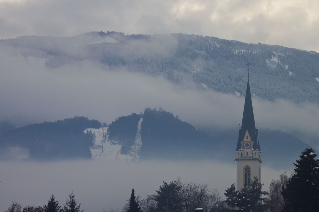 Weltcup-Strecke im dichten Nebelband und St. Andrä Kirchturm