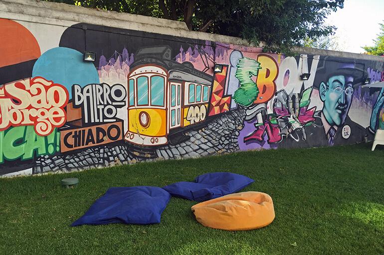 Garten mit gemütlichen Sitzsäcken und Street Art Wand.